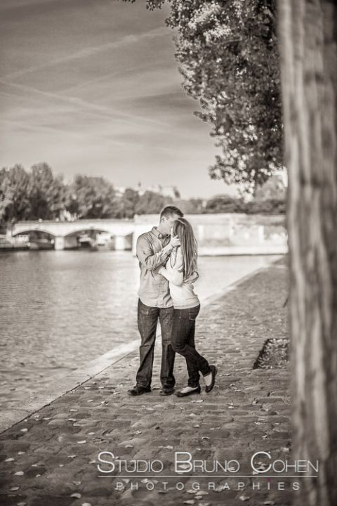portrait kissing couple stand in paris from quai de seine black and white
