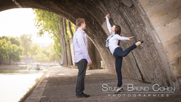 portrait dancing couple from quai de seine in paris at sunrise engagement session love at sunrise