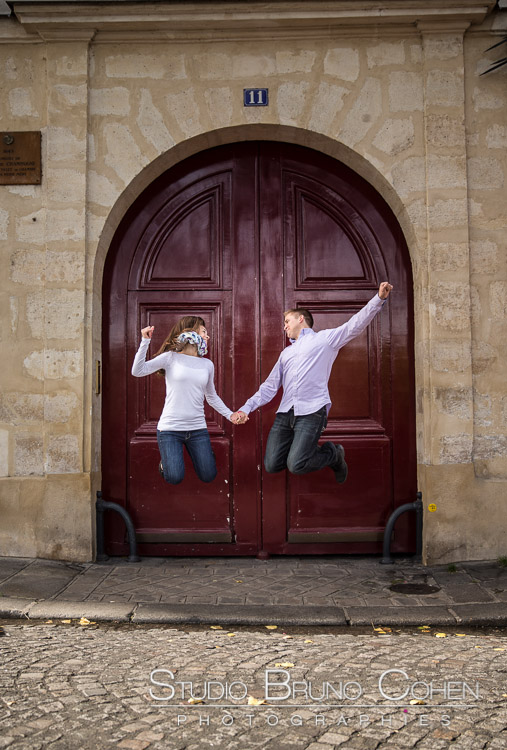 original portrait jumping couple from paris front of door proposal engagement session happy emotion smile