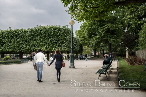proposal in paris portrait couple hand in hand walk on park near notre dame cathedral