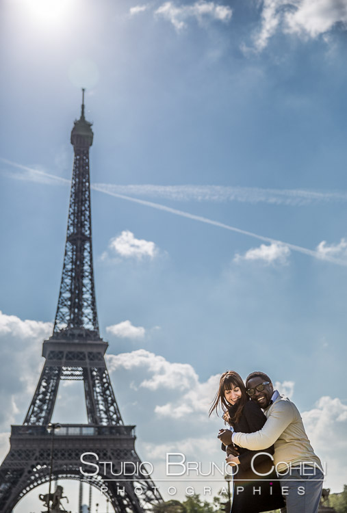 portrait couple in love smiling front of Eiffel Tower in paris blue sky