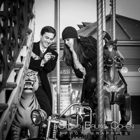 couple in love riding on horse from carousel Eiffel Tower proposal in paris black and white