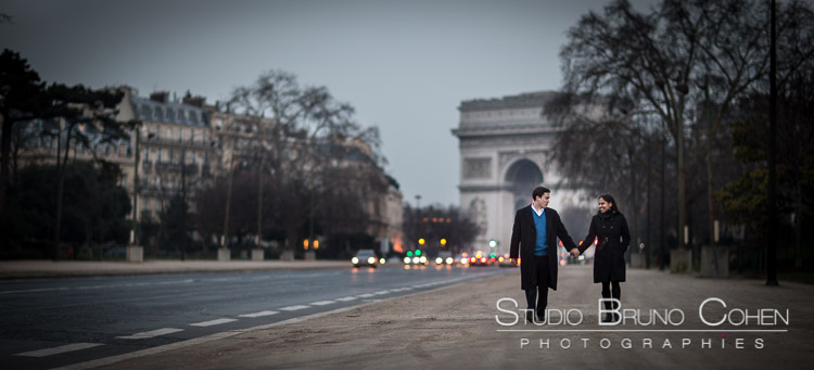 portrait couple hand in hand walk in paris front arc de triomphe at sunset proposal