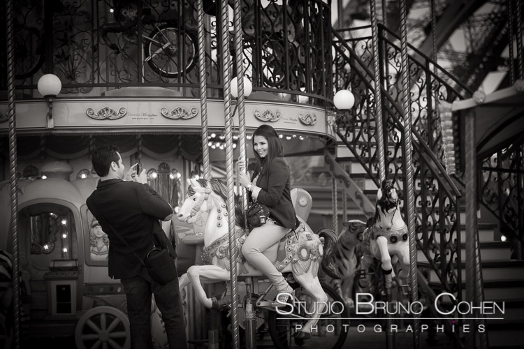 portrait couple take photo lady riding on horse from carousel Eiffel Tower in paris black and white