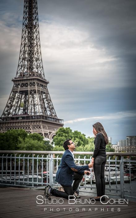 surprise proposal in paris front of Eiffel Tower blue sky