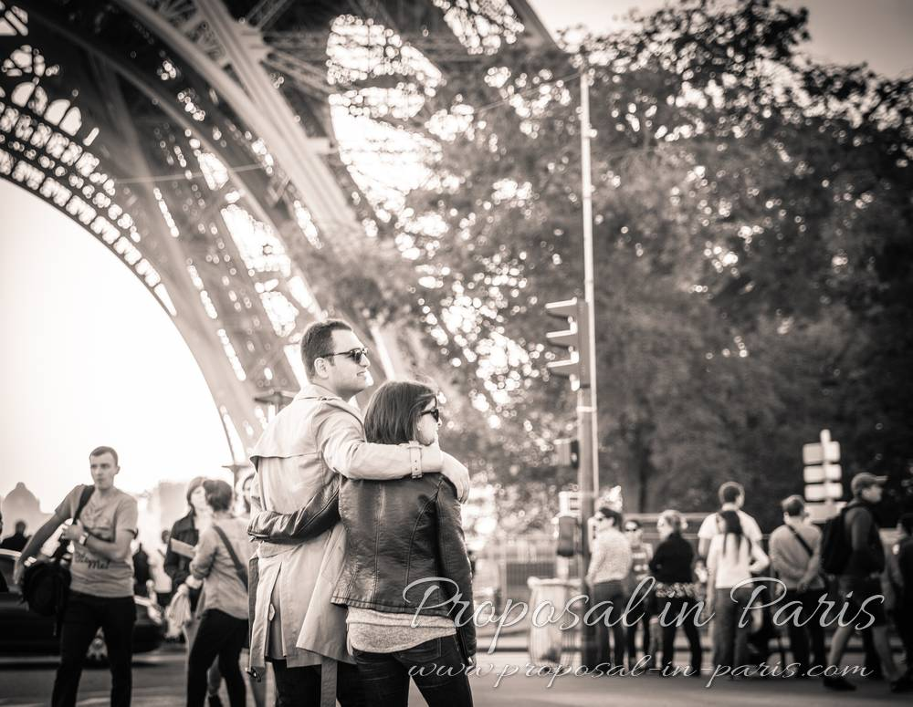 hugging couple front of eiffel tower black and white proposal in paris