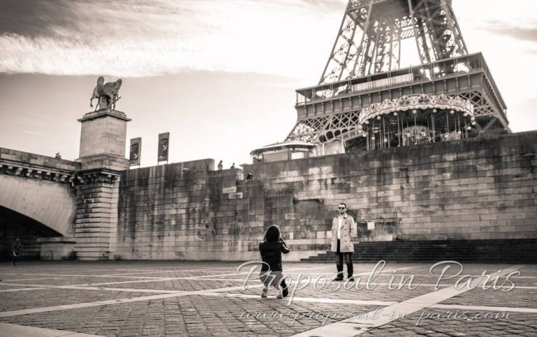 couple take picture front of eiffel tower black and white proposal in paris