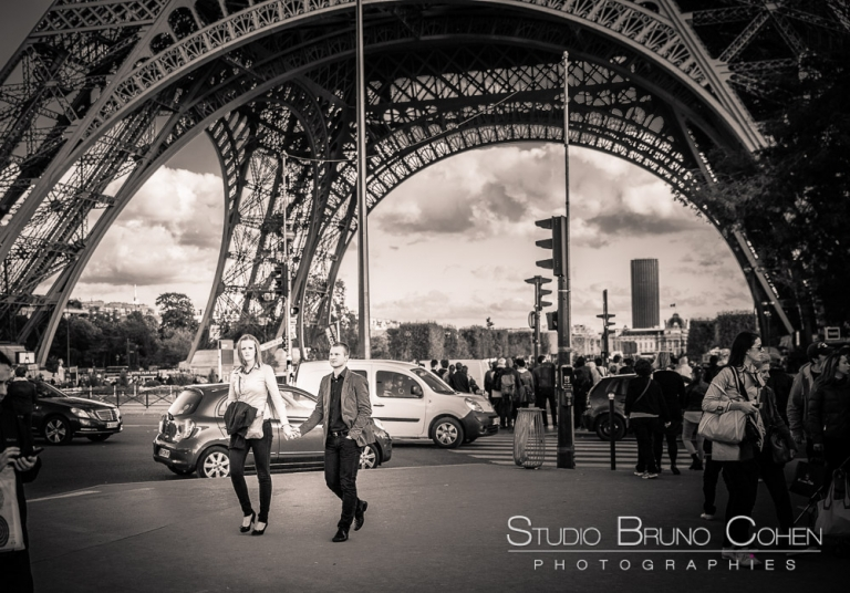 couple in love hand in hand walk in paris front of eiffel tower black and white