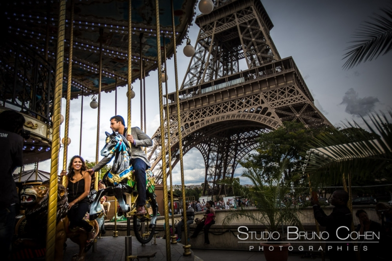 proposal in paris couple rigind horses from eiffel tower carousel at summer