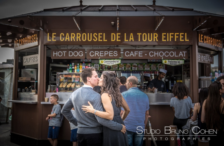 kissing couple in paris on eiffel tower carousel proposal surprise portrait kiss love