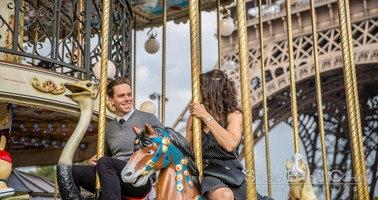 couple riding on horses at eiffel tower carousel proposal in paris