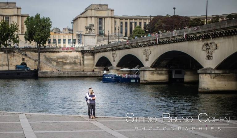 couple stand on quai de seine near eiffel tower in paris