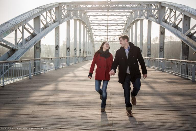 engagement photographer couple walk dewily passerelle proposal in paris at sunrise