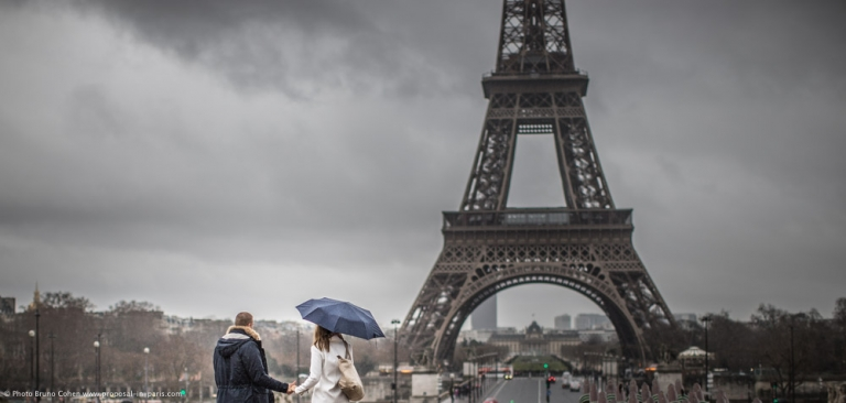 couple hand in hand in trocadero square front of Eiffel Tower under the rain proposal in Paris at winter