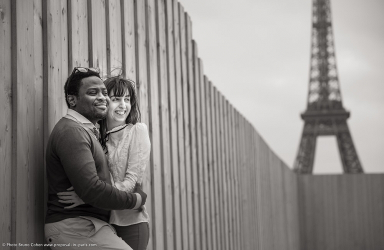 engagement session couple in love hugs from Trocadero front of Eiffel Tower in paris black and white