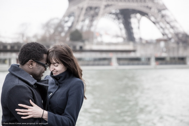 engagement session photographer paris Beloved couple face to face front of Eiffel Tower from seine banks