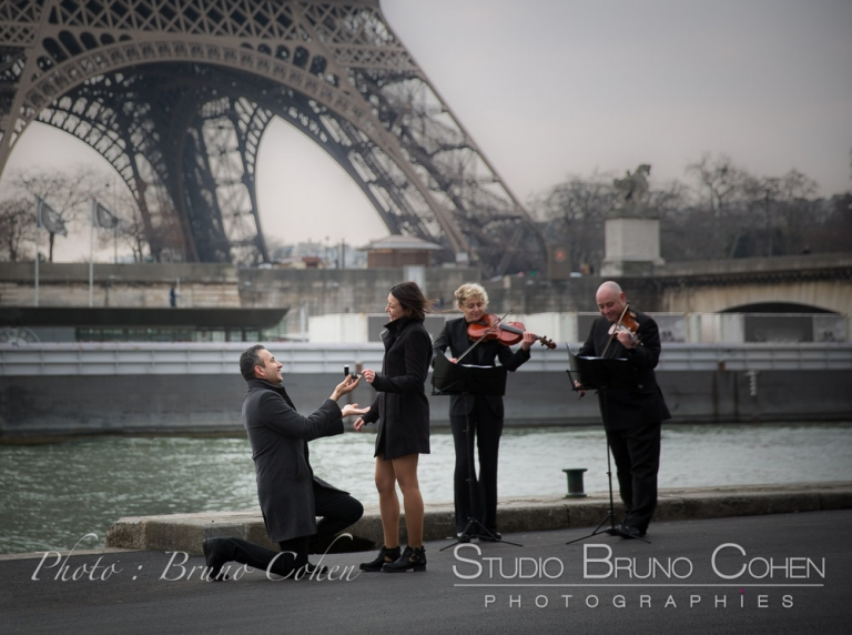 surprise proposal in paris front Eiffel Tower musicians violinists emotions couple in love