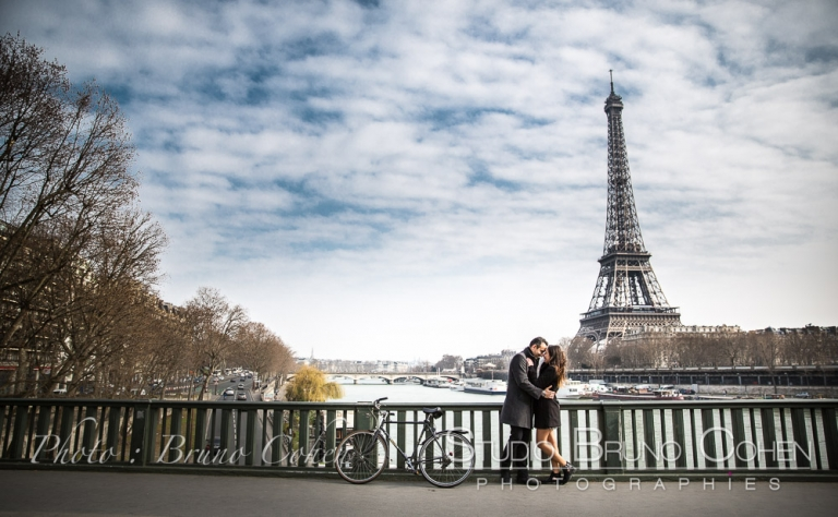 proposal in paris kissing couple from de Bir-Hakeim bridge at daylight front of Eiffel Tower blue sky
