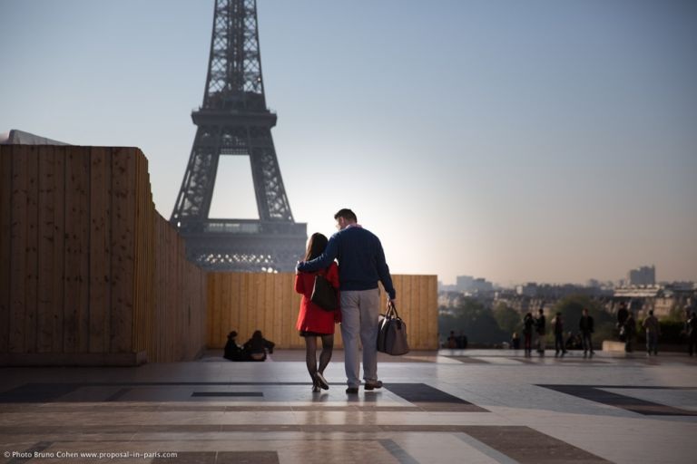 couple walk on Trocadero front of Eiffel Tower in love at sunrise