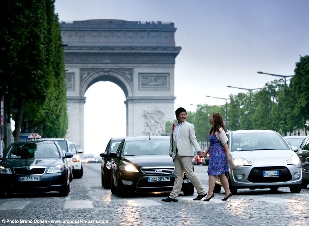 proposal in paris couple asian crossing road at sunrise arc de triomphe hand and hand