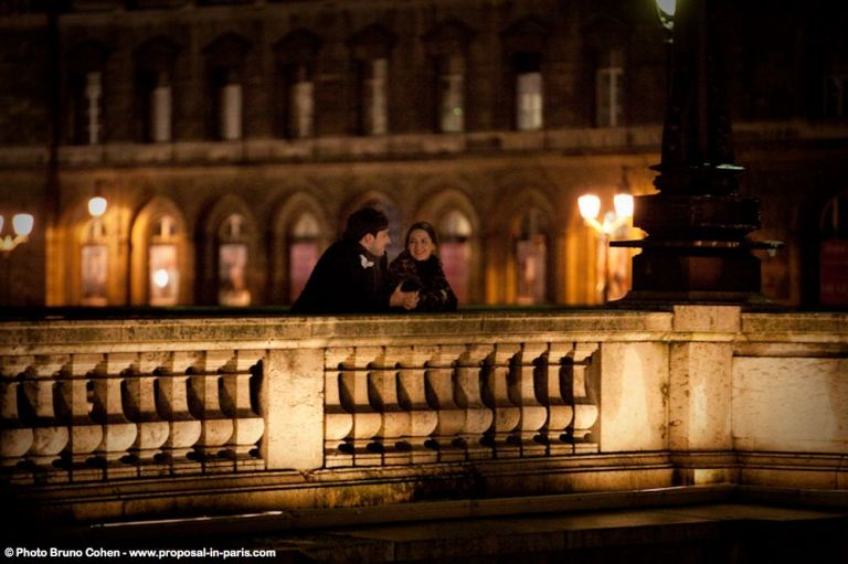 portrait couple in love on bridge at night in paris proposal