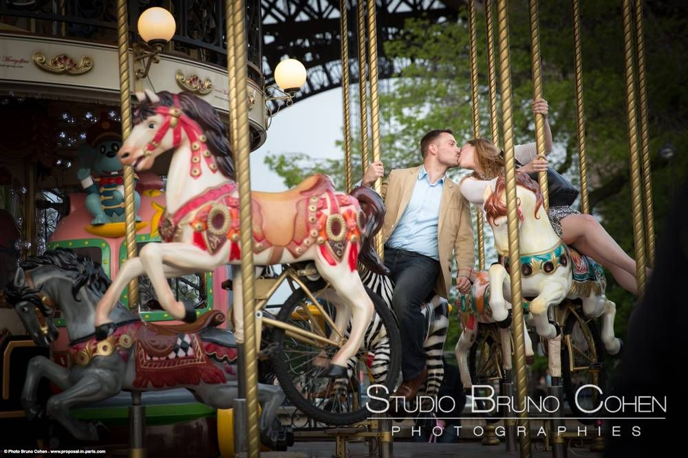 portrait kissing couple ride on horses from carousel Eiffel Tower love engagement proposal