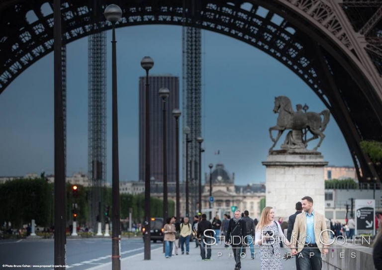 portrait couple hand in hand walking front of Eiffel Tower in paris proposal at sunset
