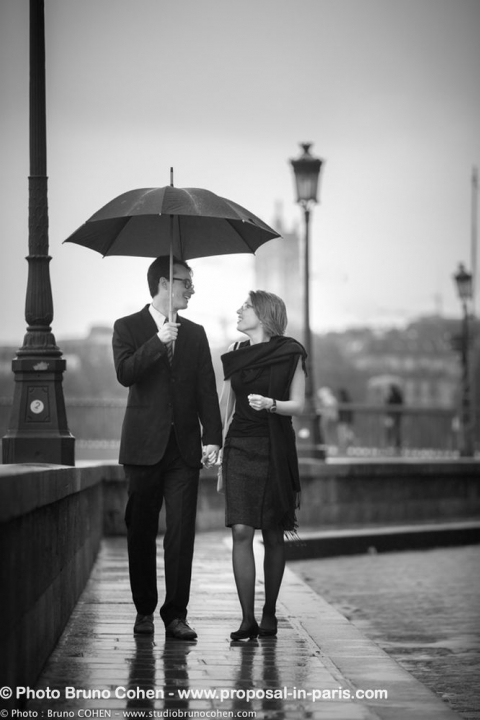 portrait couple walking in paris umbrella cloudy black and white