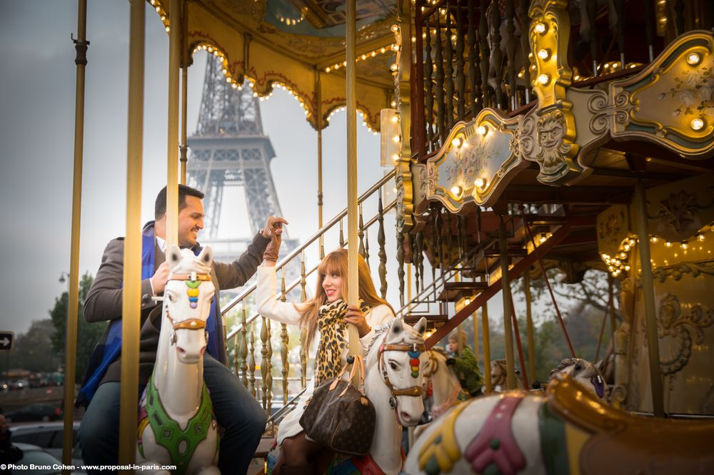 portrait couple riding in horses at carousel front Eiffel Tower in paris love funny moment smile happy