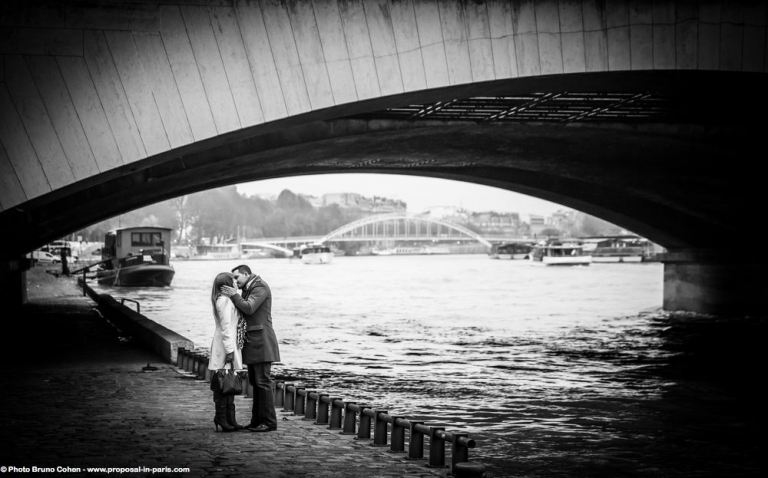 portrait kissing couple from quai de seine near Eiffel Tower in paris engagement session love happy emotions
