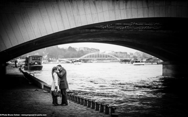 portrait kissing couple from quai de seine near Eiffel Tower in paris engagement session love happy emotions