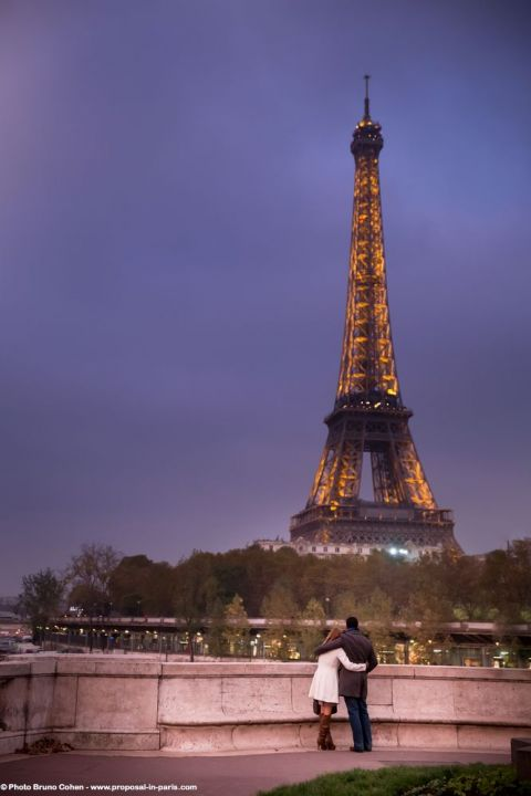 portrait hugging couple in love front of Eiffel Tower at sunset winter