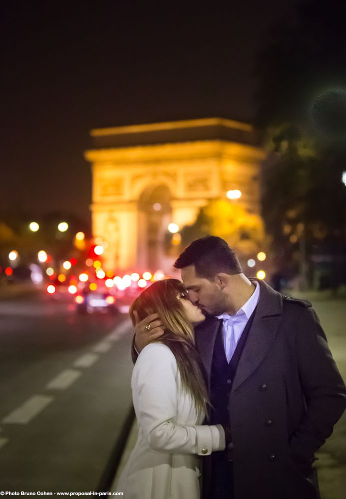 portrait couple kissing in love in paris front of arc de triomphe on road summer night