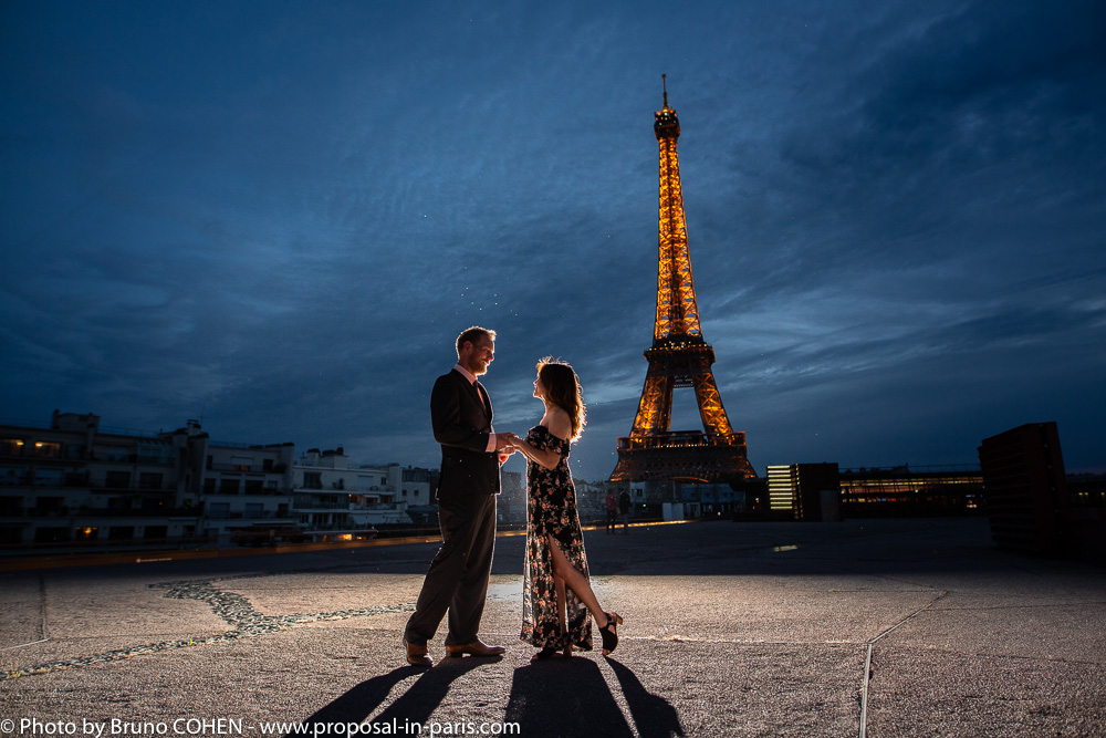 surprise proposal in paris focus couple look each other front of Eiffel Tower at night