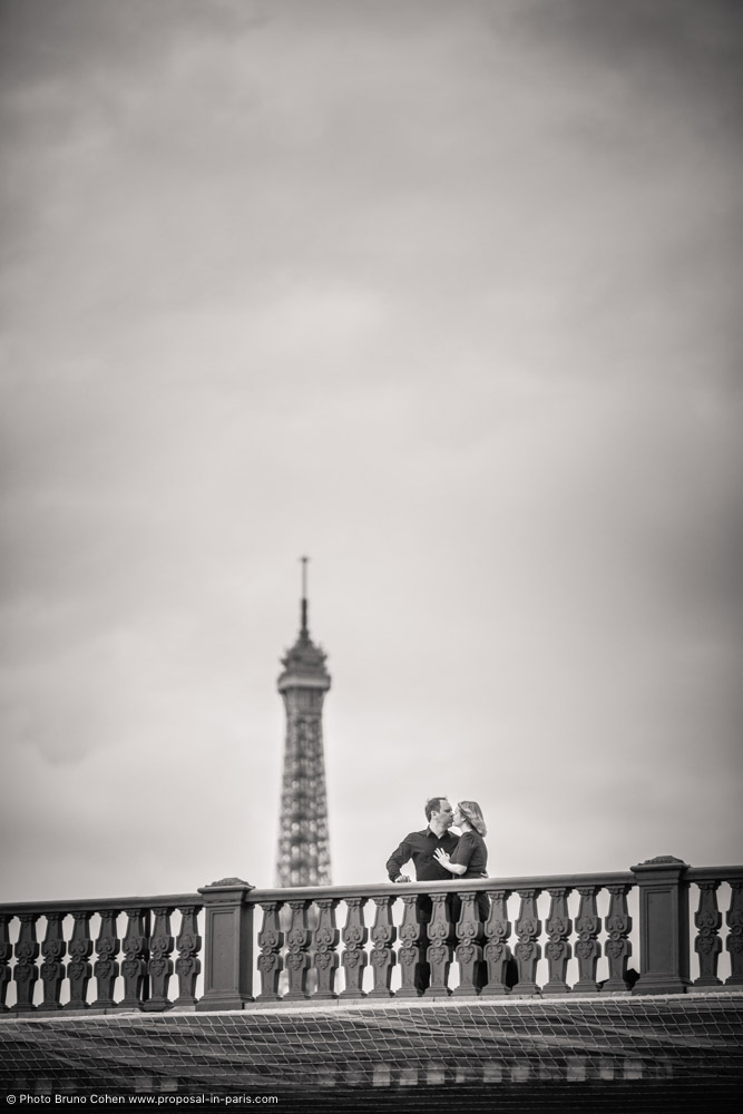 proposal in paris kissing couple front of Eiffel Tower bridges black and white