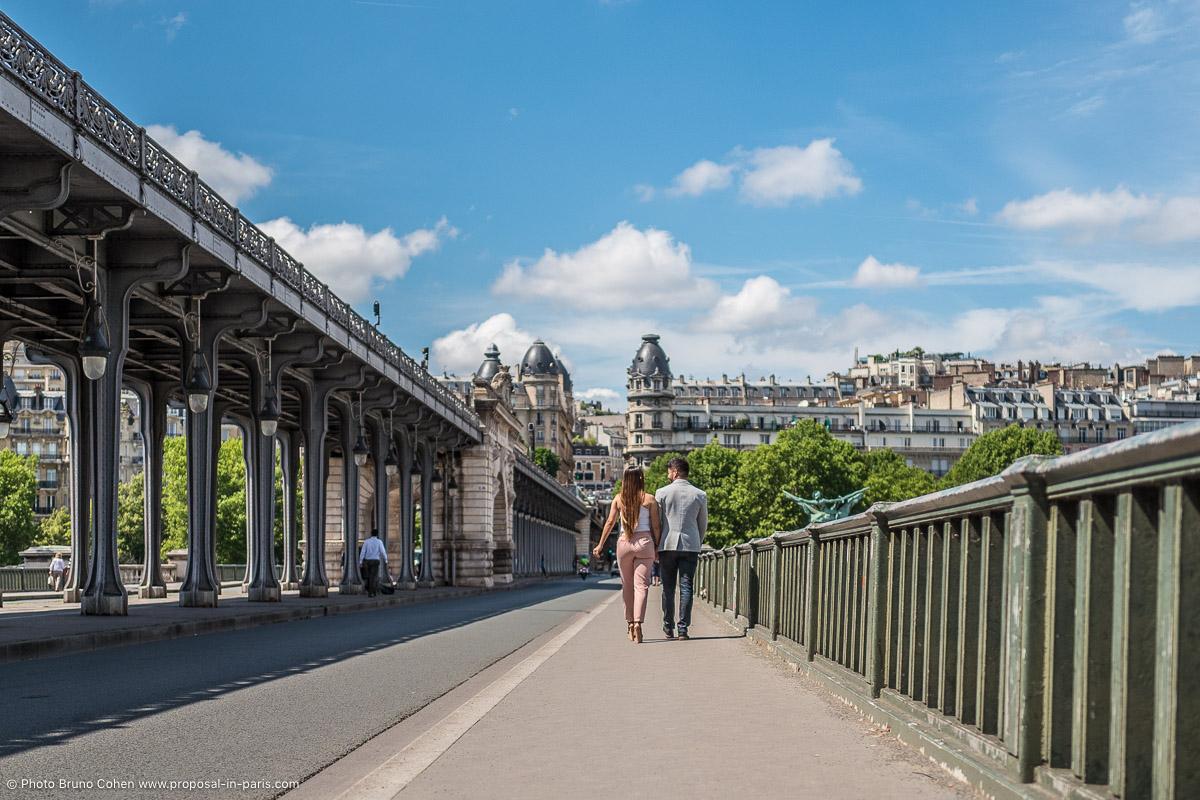 proposal in paris couple holding hands bir hakeim bridge blue sky summer