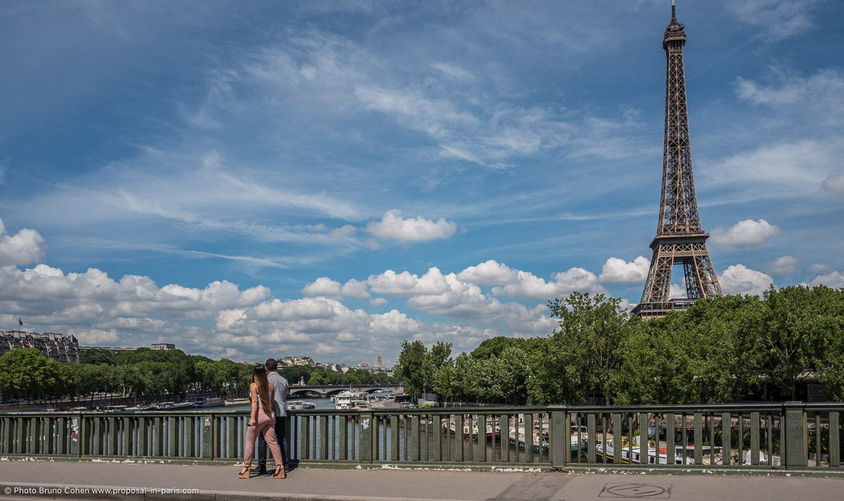 proposal in paris couple walking front of Eiffel Tower blue sky
