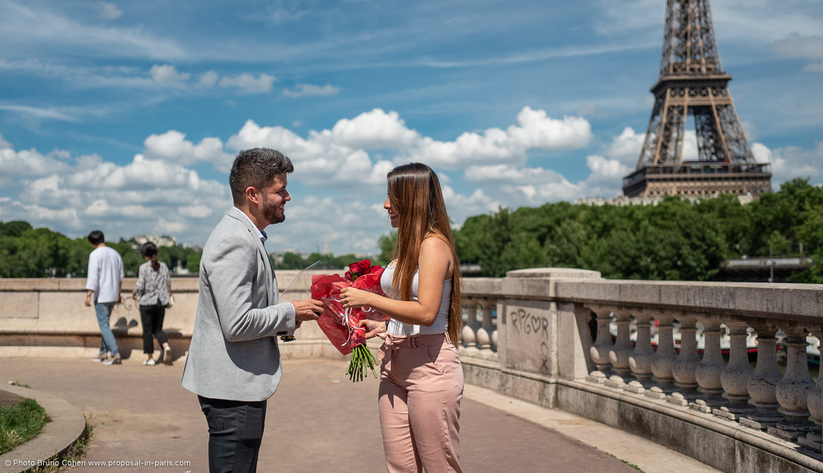 surprise proposal in paris couple ring red roses front of Eiffel Tower blue sky