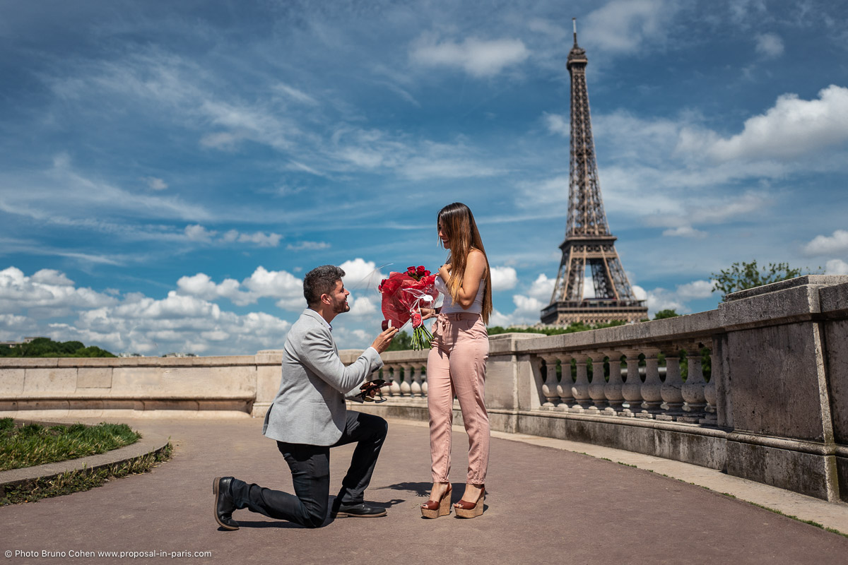 surprise proposal in paris red roses couple ring front Eiffel Tower blue sky