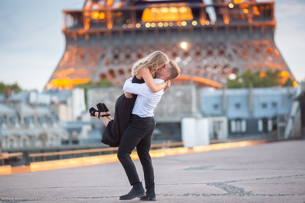 amazing proposal in paris couple in love kissing from rooftop front of Eiffel Tower at sunset