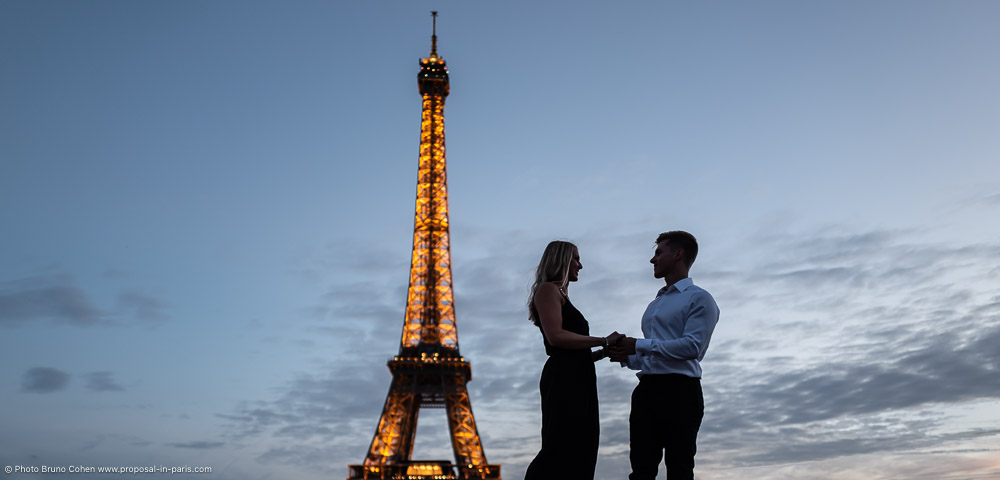 portrait couple holding hands front of Eiffel Tower at sunset