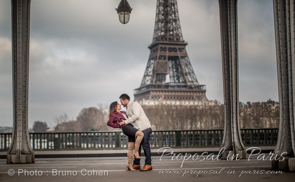 winter proposal in paris couple dancing in love from bir hakeim bridge front of Eiffel Tower