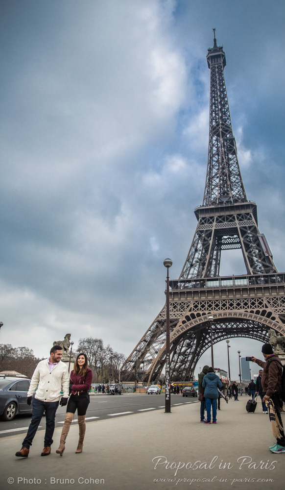 couple in love walking in paris during winter surprise proposal in paris front of Eiffel Tower