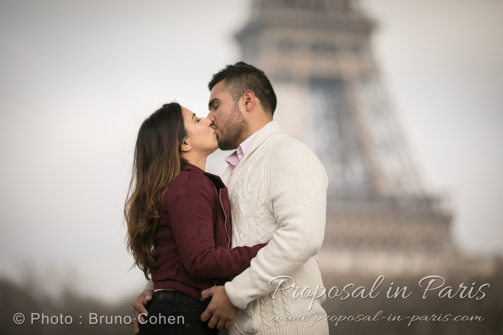 winter proposal in paris kissing couple front of Eiffel Tower