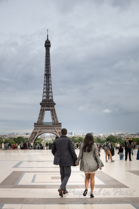 couple holding hands walk from Trocadero front of Eiffel Tower