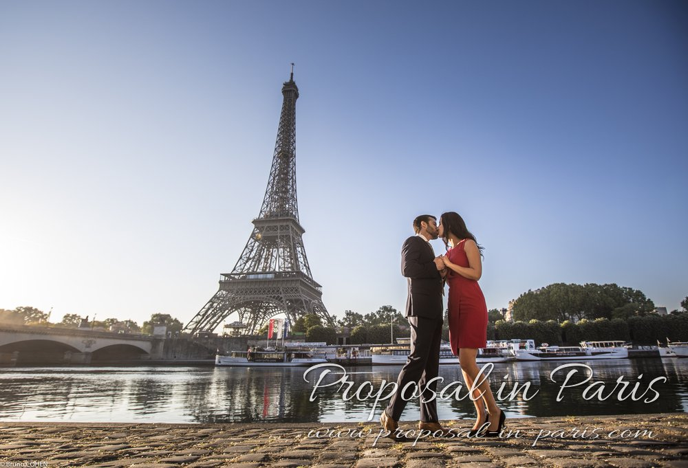 kissing couple hand in hand standing from quai de seine front of Eiffel Tower at sunrise