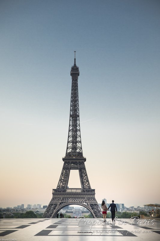 couple holding hands walking alone from Trocadero front of Eiffel Tower at sunrise