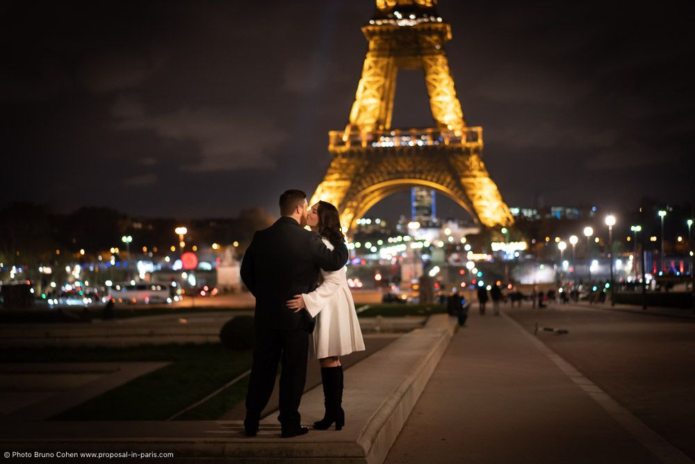 kissing couple in front of Eiffel Tower by night