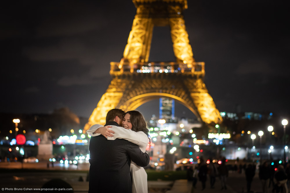 hugging couple front of Eiffel Tower at night