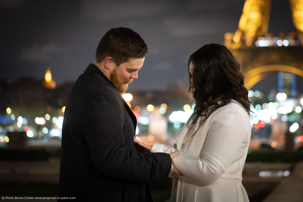 after proposal couple look the ring front Eiffel Tower at night